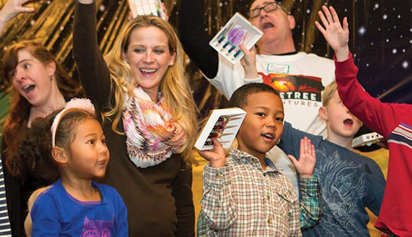 Kids and adults laugh and celebrate a successful Christmas production together at the Cast Party