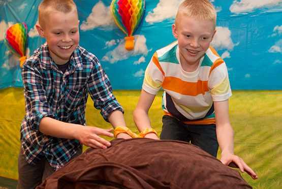 Move the Stone Station Photo: Two boys work together to manuver a giant pillow 'stone' through an obsticle course.