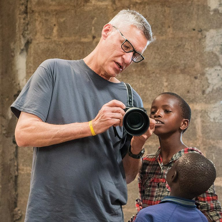 Thom showing African kids his camera at a mission trip