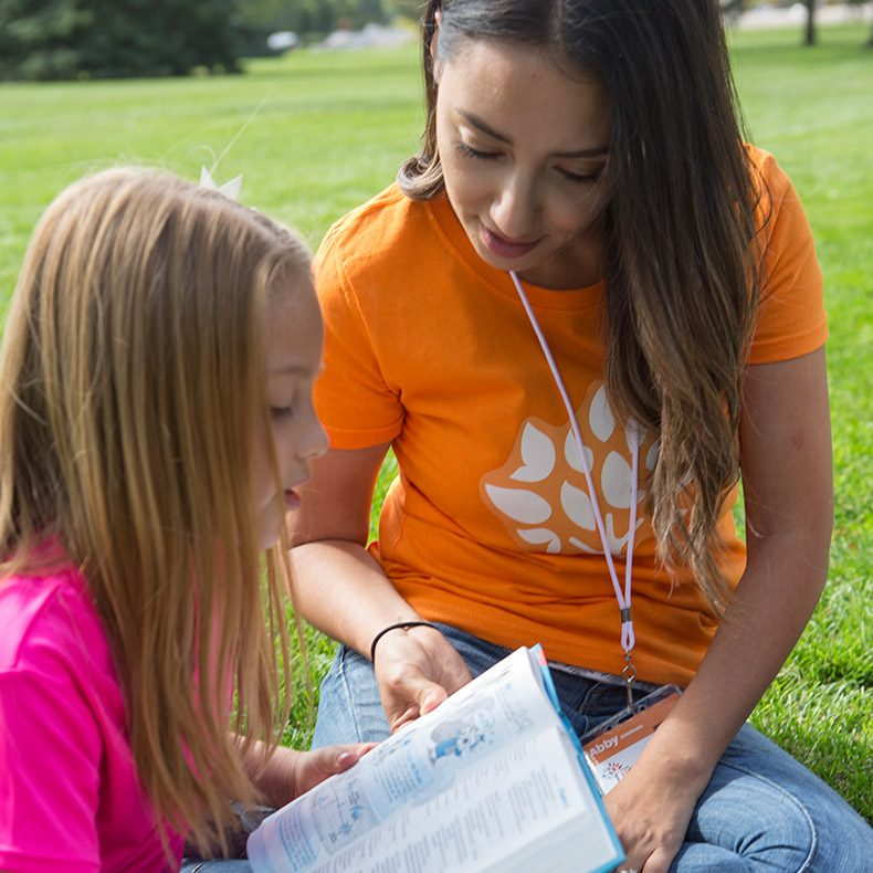 Day Camp Director Reading Scripture with Girl