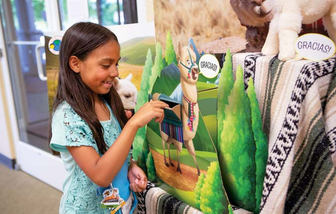 a young girl drops a donation into a VBS operation kid to kid donation display with a llama who says Gracias
