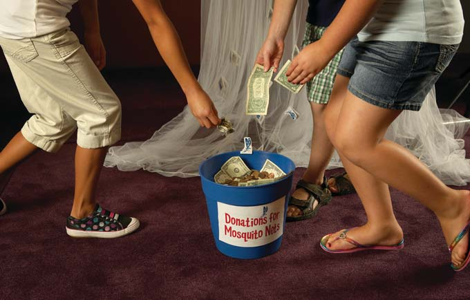 kids hands and feet gather around dropping cash into a bucket that says Mosquito Net Donations
